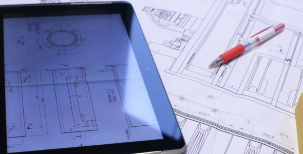 Pan Over Blueprints and Tablet