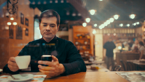 Young Man Using Phone And Having Coffee In A Cafe