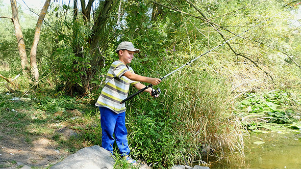 Boy Fishing With Spinning On The River
