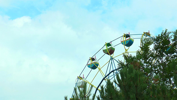 Ferris Wheel on the Background Moving Clouds