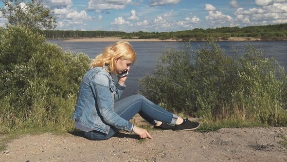 Girl Speaks on the Phone Near the River