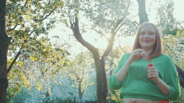 Happy Pregnant Woman Blowing Bubbles In Bloomy