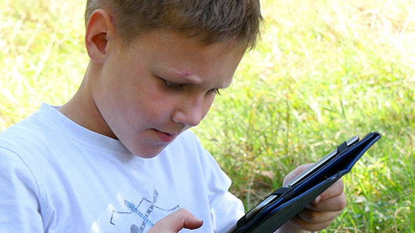 Happy Young Boy Using Tablet