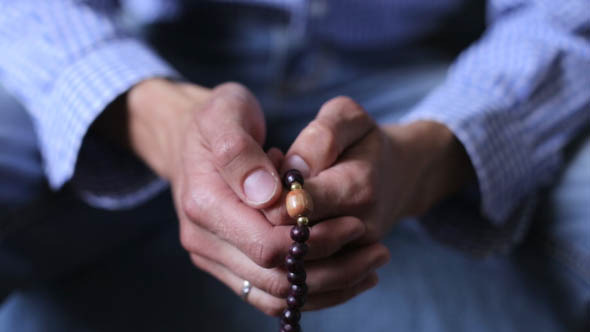 Man Prays the Rosary