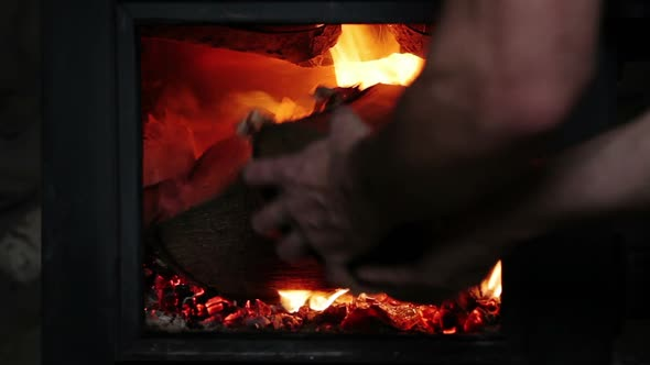 Man Putting Log Woods Inside A Fireplace