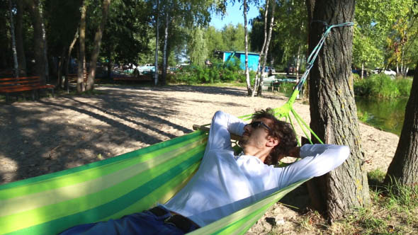 Man Rests in a Hammock on the Beach