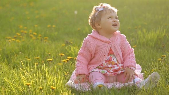 Portrait Of A Baby Sitting On The Green Grass