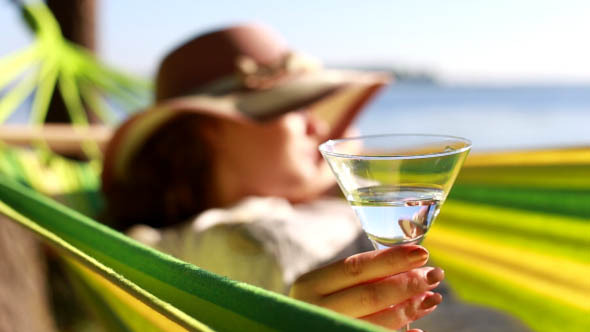 Woman Drinking a Glass on the Beach